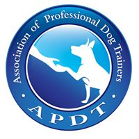 APDT Logo with a human hand and a dog reaching for each other on a blue background with the words association of Professional Dog Trainers Above the cirlcle